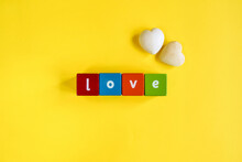 Love - Word Made Of Colored Wooden Cubes. Nearby There Are Two Decorative Stone Hearts. Close-up. Top View. Copy Space. Selective Focus.