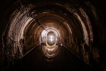 Flooded Round Sewer Tunnel With Water Reflection