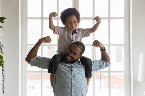 Fototapeta Happy funny kid riding on dads shoulders. African American daddy wearing glasses and son playing together, showing hand strength, flexing biceps, laughing and having fun. Family home activity concept obraz