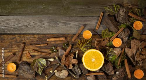 Fototapeta Tło z drewnianych desek wraz z dekoracją liście gałązki kamienie pomarańcz i laski cynamonu obraz