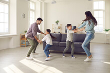 Happy Family Spending Quality Time At Home. Couple With Children Playing, Dancing And Having Fun In Big New Room. Little Boy, Girl And Parents Enjoying Leisure In Covid19 Coronavirus Lockdown Together