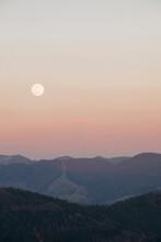 Scenic Full Moon Above Mountain Peaks With Sunset Orange Sky.