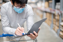 Asian Man Worker Wearing Face Mask Doing Stocktaking Of Product In Cardboard Box On Rack In Warehouse By Using Clipboard. Physical Inventory Count And Preventing The Spread Of COVID-19 (Coronavirus).
