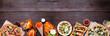 Leinwandbild Motiv Healthy plant based fast food bottom border. Top view over a dark wood banner background. Table scene with cauliflower crust pizzas, bean burgers, mushroom tacos and vegetarian sides. Copy space.