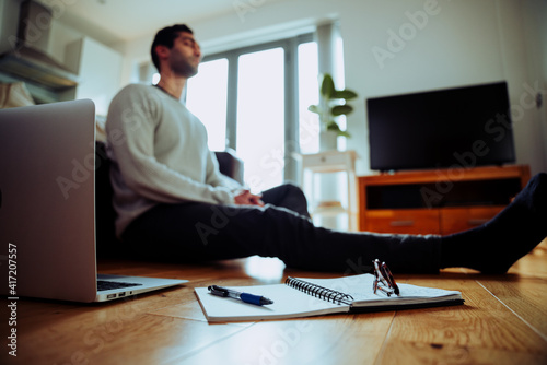 Obraz na plátně Mixed race business man working from home sitting on lounge floor with eyes clos