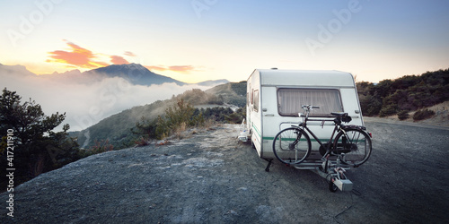 Caravan trailer with a bicycle near mountain lake Lac de serre-poncon in French Alps at sunrise Fotobehang