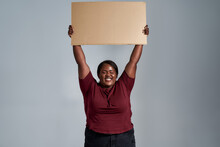 Excited Plus Size Young African American Woman In Casual Clothes Looking At Camera With A Smile, Holding Blank Cardboard Banner Above Her Head, Posing Isolated Over Gray Background