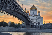 Cathedral Of Christ The Saviour In Moscow In Orange Sunset Light. Patriarch Bridge. The Bridge Leads To The Temple. Traveling To Moscow, Russia.