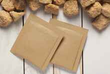 Blank Brown Paper Square Sachet And Sugar Cubes On Plank Tabletop. 3D Rendering And Photo.