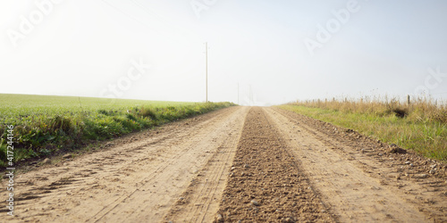 Fototapeta An old country dirt road through the village and fields to the forest in a fog. Autumn rural scene. Transportation, agriculture, farm, ecology. countryside, ecotourism, road trip, logistics, distance obraz