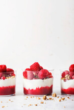 3 Layered Yogurt Parfaits On A White Background With Home-made Granola, Raspberry Purre And Fresh Raspberries And Cranberries.