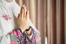 A Muslim Woman Wearing Moslem Clothes With Hijab And Rosary, Praying In The Mosque, Muslim Woman Raising Hand Pray.