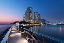 Seaside Promenade And High Rise Residential Building In Hong Kong City At Dusk