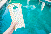 Prefilter Pump Basket In Girl Hand Over Blurred Blue Swimming Pool Water Background, Swimming Pool Service And Maintenace Concept, Pool Pump Accessories