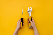 Female Hands Holding A Wrench And A Screwdriver On Yellow Background.