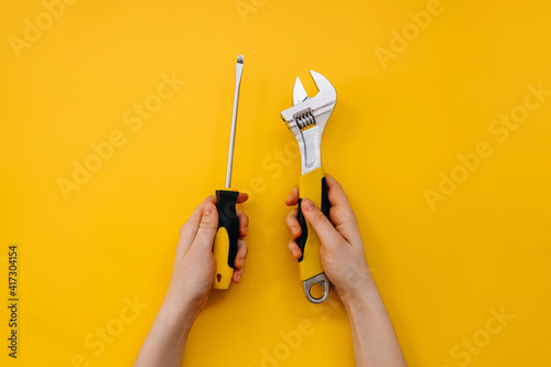Stampa su Tela Female hands holding a wrench and a screwdriver on yellow background