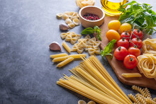 Mixed Dried Pasta Selection On Wooden Background. Composition Of Healthy Food Ingredients Isolated On Black Stone Background, Top View, Flat Lay.