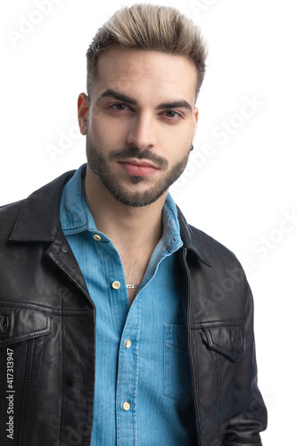 cool young biker man in leather jacket posing isolated in studio © Viorel Sima