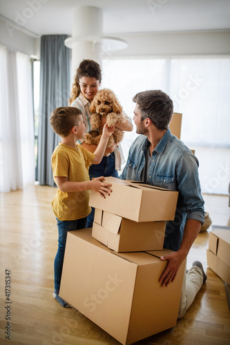 Happy family with children moving with boxes in a new apartment house. Wall mural