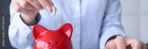 Woman counting on calculator and putting coin in piggy bank closeup Fototapet