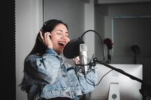 Asian Female Singer With A Passion For Music And Microphone. While Singing Recorded In A Professional Studio Music Concept