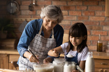 Smiling Mature Hispanic Granny And Small Granddaughter Work With Flour Bake Cookies In Kitchen At Home. Happy Caring Senior Grandmother And Little Grandchild Cook Breakfast Or Dessert Together.