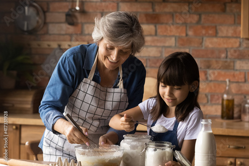 Fotografia, Obraz Smiling mature Hispanic granny and small granddaughter work with flour bake cookies in kitchen at home