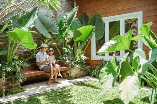 Slika na platnu portrait of asian family enjoy their time at tropical backyard at home