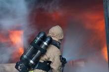 Firefighter Holding Hose And Spraying Water