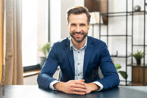 Young bearded confident successful man in business casual clothes looking at camera, skilled job applicant is ready for an online interview on a video call, sitting at the desk, holding hands together