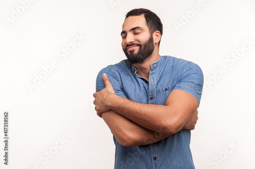 Fototapeta Selfish narcissistic man with beard hugging itself, comforting and supporting, fulfilling his needs to feel happiness, self esteem