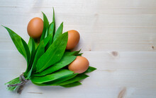 Bunch Of A Ramson And Chicken Eggs, Fresh Raw Wild Garlic On Light Wooden Background