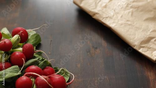 Fototapeta Rzodkiewka w pęczku na stole drewnianym brązowym obraz