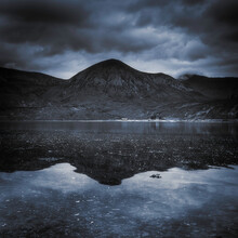 Dramatic Sky Over Beinn Bhreac Reflecting In Loch Na Dal On The Isle Of Skye.The Rough Landscape Of Scotland On A Gloomy Day.Dark Nature Photo With Atmospheric Mood And Blue Tones.