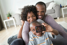 Parents And Son Photographing Themselves With Digital Camera