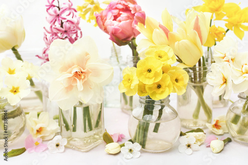 Spring blossoming daffodils, tulips and flowers light bright background, pastel and soft springtime floral card, selective focus, toned © ulada