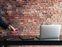 Mesa Con Ordenador Y Teléfono  Y Una Mano De Trabajador Sosteniendo Unos Rotuladores