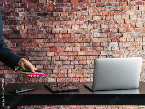 Obraz na plátně mesa con ordenador y teléfono  y una mano de trabajador sosteniendo unos rotulad