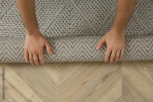 Obraz Man rolling out new carpet flooring indoors, top view. Space for text - fototapety do salonu
