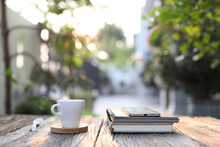 White Coffee Cup With Phone And Notebook On Wooden Table At Outdoor