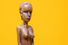 Sideview Closeup Of Female Figurine Carved Out Of Ebony Wood Without Clothes On Holding Hands In Front Of Her Private Area Against A Seamless Yellow Background.