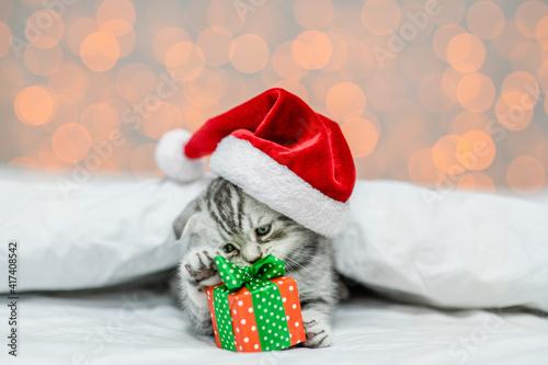 Playful kitten wearing red santa hat lying under white blanket on festive background with gift box © Ermolaev Alexandr