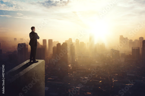 Canvas Print Confident businessman standing on building rooftop