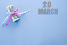Calendar Date On Blue Background With Rolled Up Dollar Bills Pinned By Blue And Pink Ribbon With Copy Space. March 20 Is The Twentieth Day Of The Month