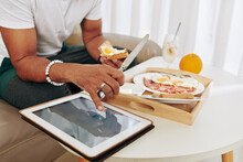 Close-up Image Of Man Eating Breakfast And Checking Stock Market Data On Scren Of Tablet Computer
