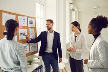 Business Team Analyzes Sales Graphs And Charts, Develops A New Strategy, Discussing Work Issues. Young Project Manager Makes A Suggestion Or Points Out A Mistake At The Meeting. Concept Of Teamwork.