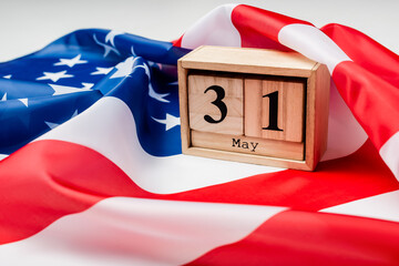 Close up view of calendar with 31 may date on american flag on blurred foreground on grey background