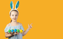 Happy Easter, Kids. A Girl In Bunny Ears On Her Head Holds A Tray With Eggs Of Blue And Yellow Color, The Emotion Of Surprise On Her Face. The Index Finger Points To An Empty Space
