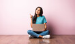 Indian asian girl using laptop while sitting against pink wall on wooden floor