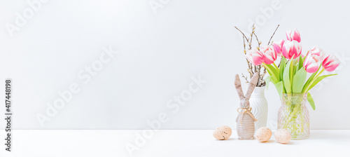 Fototapeta premium Home interior with easter decor. Pink tulips in a vase, easter eggs on a light background
